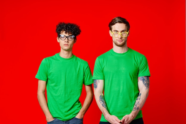 Dois amigos em camisetas verdes estão lado a lado, posando de fundo vermelho de amizade