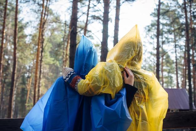 Dois amigos em capas de chuva em pé de costas para a câmera em um estacionamento de turistas na floresta. mulheres com capas de chuva coloridas descansam durante uma caminhada. conceito de acampamento.