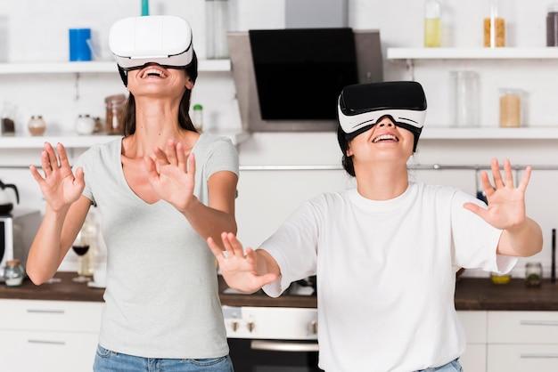 Dois amigos em casa se divertindo com fone de ouvido de realidade virtual