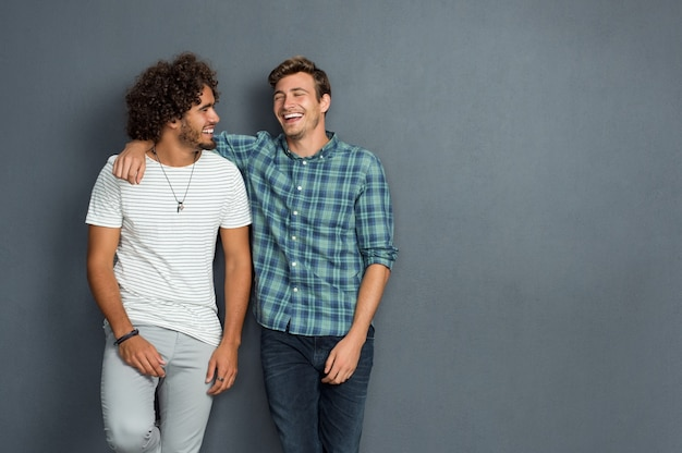 Dois amigos em roupas casuais em pé e rindo juntos