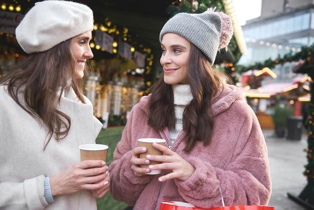 Dois amigos em um mercado de natal bebendo vinho quente