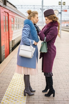 Dois amigos estão em um casaco na plataforma da estação ferroviária