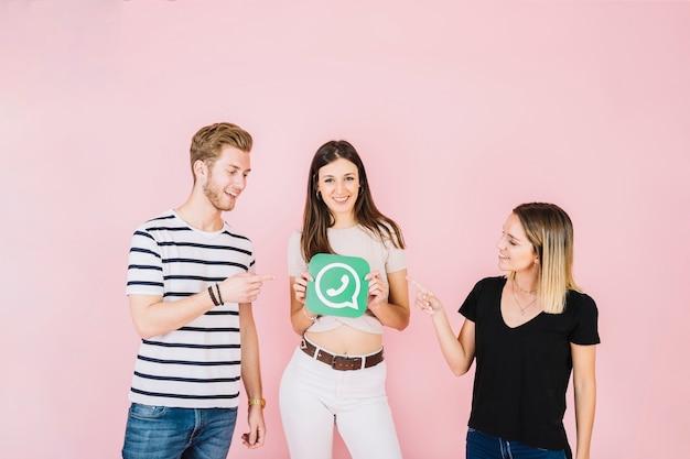 Dois amigos felizes, apontando para a mulher segurando o ícone do whatsapp
