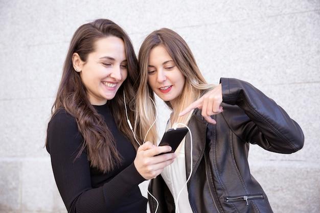 Dois amigos felizes compartilhando um telefone celular para ouvir música juntos na rua.
