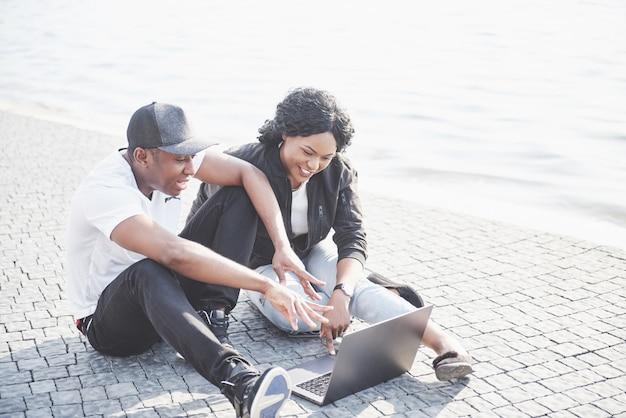 Dois amigos felizes de estudantes ou parceiros de negócios estão sentados ao ar livre e desfrutando de um laptop