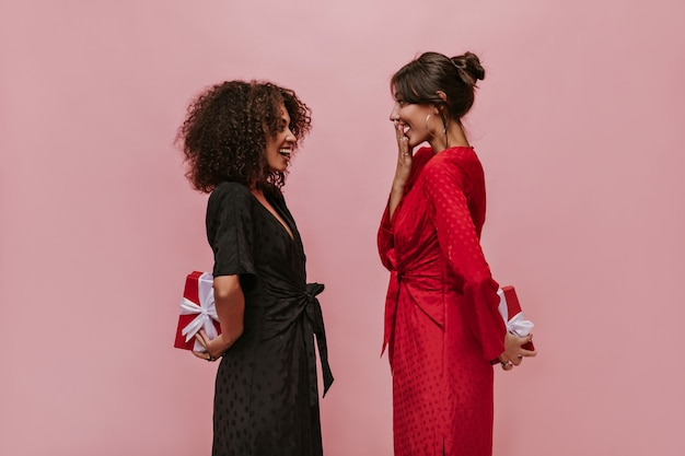 Dois amigos felizes e maravilhosos em vestidos de bolinhas vermelho e preto olhando um para o outro e segurando caixas de presente atrás na parede rosa