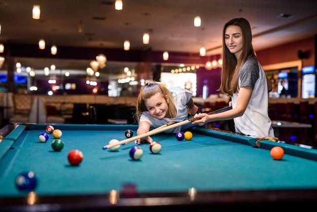 Dois amigos felizes em um bar jogando bilhar
