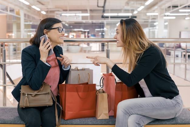 Dois amigos felizes mulheres adultas com sacos de compras