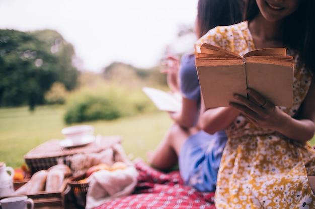 Dois amigos fêmeas que apreciam o piquenique junto em um parque.