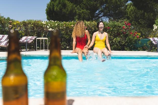 Dois amigos fêmeas que têm o divertimento na piscina.
