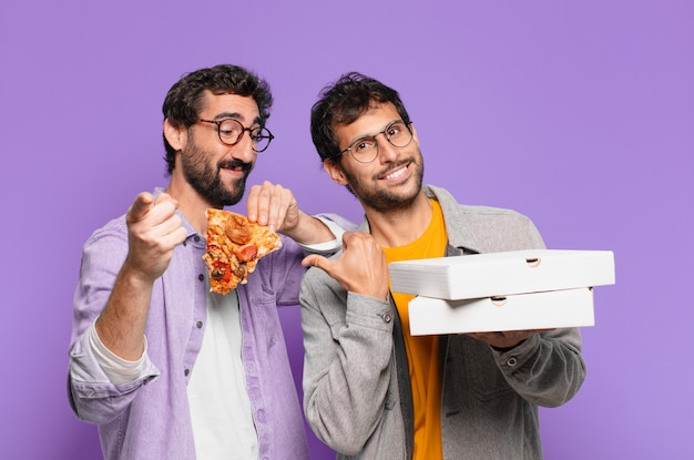 Dois amigos hispânicos apontando ou mostrando e segurando pizzas para levar