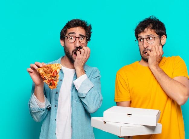 Dois amigos hispânicos com expressão de medo e segurando pizzas para levar
