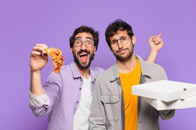 Dois amigos hispânicos com expressão de surpresa e segurando pizzas para levar