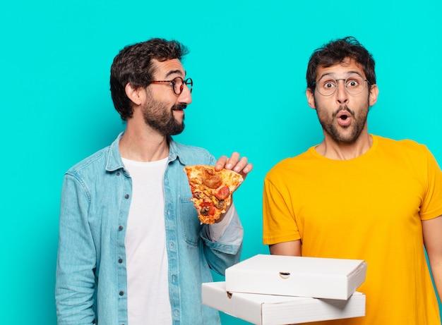 Dois amigos hispânicos com expressão de surpresa e segurando pizzas para viagem