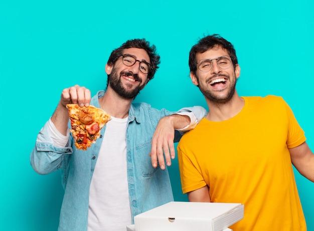 Dois amigos hispânicos com expressão feliz e segurando pizzas para viagem