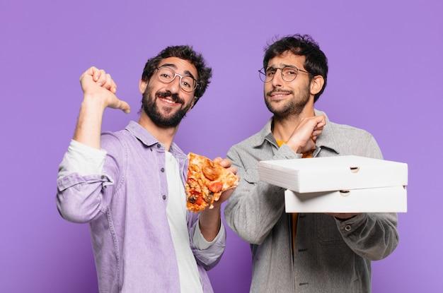 Dois amigos hispânicos com uma expressão feliz e segurando pizzas para levar