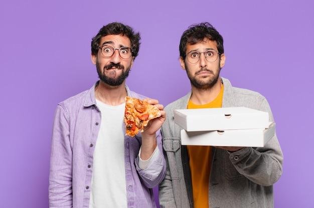 Dois amigos hispânicos com uma expressão triste e segurando pizzas para levar