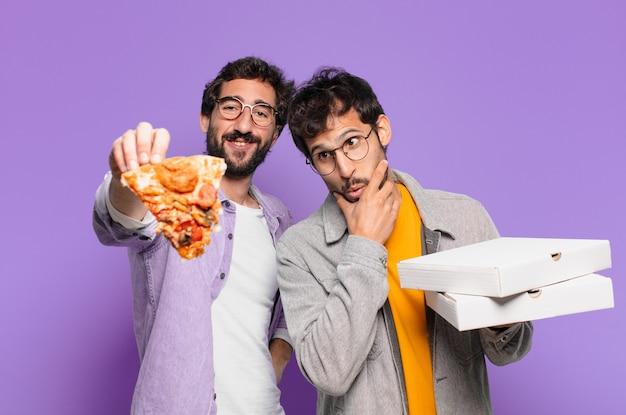 Dois amigos hispânicos pensando em expressão e segurando pizzas para levar