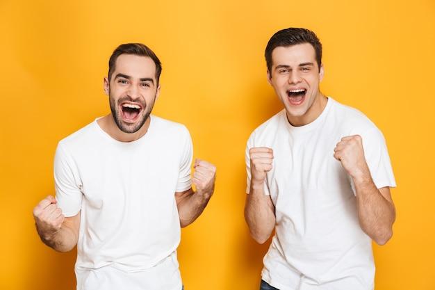 Dois amigos homens alegres e animados com camisetas em branco, isolados na parede amarela, comemorando o sucesso