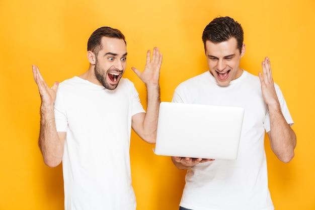 Dois amigos homens alegres e animados, vestindo camisetas em branco, isolados sobre uma parede amarela, usando um computador laptop, comemorando o sucesso
