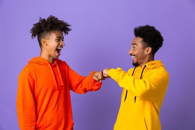 Dois amigos homens felizes com moletons coloridos