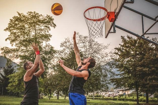 Dois amigos jogam basquete.