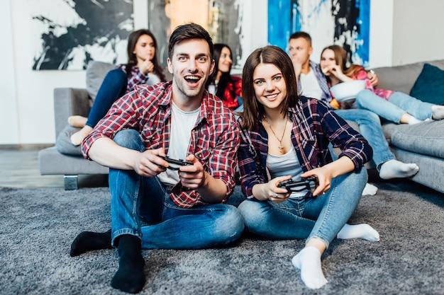 Dois amigos jovens felizes segurando o joystick e jogando videogame. tempo feliz