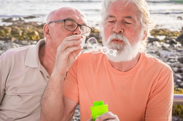 Dois amigos maduros e velhos brincando com bolhas de sabão na praia com o mar ao fundo - sêniors caucasianos