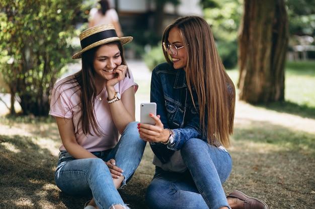 Dois amigos meninas, sentando, parque