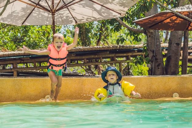 Dois amigos meninos pulando na piscina