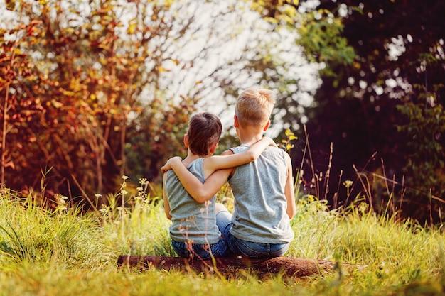 Dois amigos meninos se abraçam em dia ensolarado de verão.