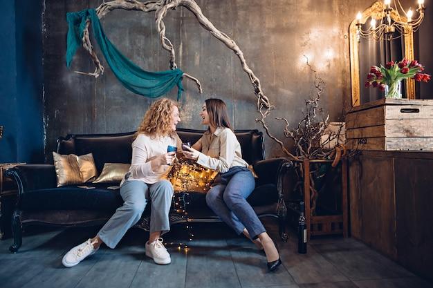 Dois amigos ou irmãs discutem com entusiasmo algo sentado no sofá em um ambiente aconchegante e festivo, com um copo de vinho.