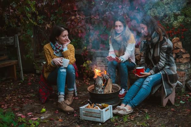 Dois amigos relaxam e bebem vinho confortavelmente em uma noite de outono, ao ar livre, perto da lareira no quintal.