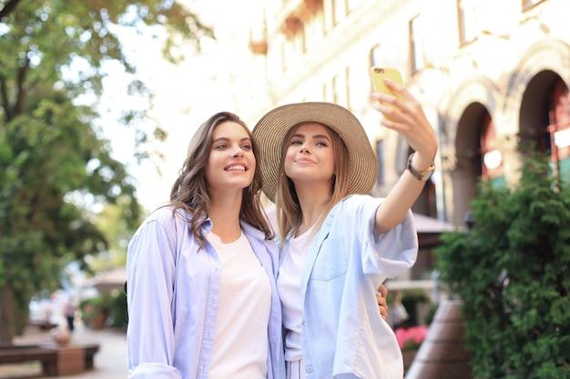Dois amigos rindo, aproveitando o fim de semana juntos e fazendo selfie no fundo da cidade.