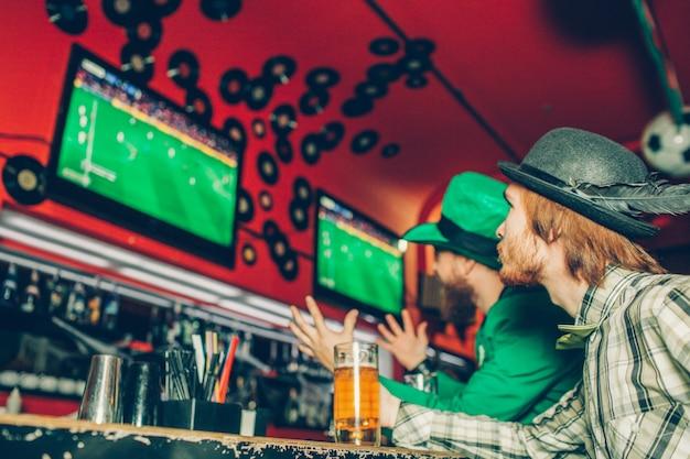 Dois amigos se sentam no balcão de bar no pub e assistir jogo de futebol. eles sérios e concentrados. um deles usa traje verde de são patrício. caneca de cerveja stand no balcão de bar.