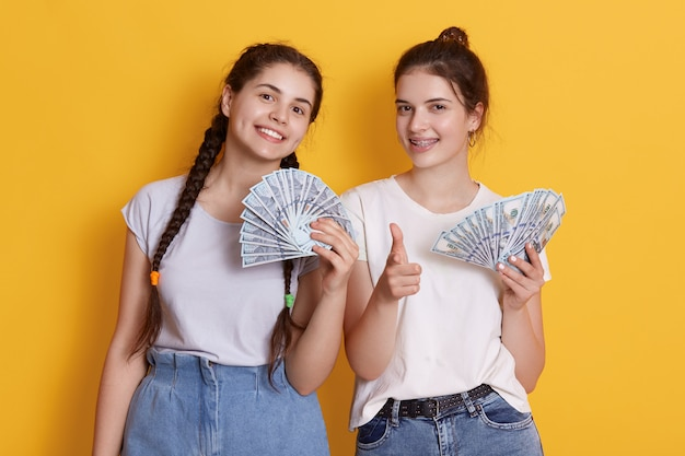 Dois amigos segurando dinheiro nas mãos, com feliz expressão facial
