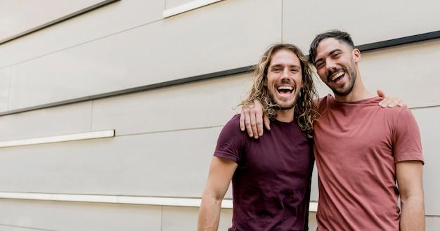 Dois amigos sorridente, olhando para a câmera