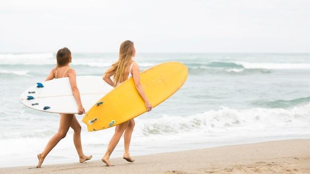 Dois amigos sorridentes correndo na praia com pranchas de surf