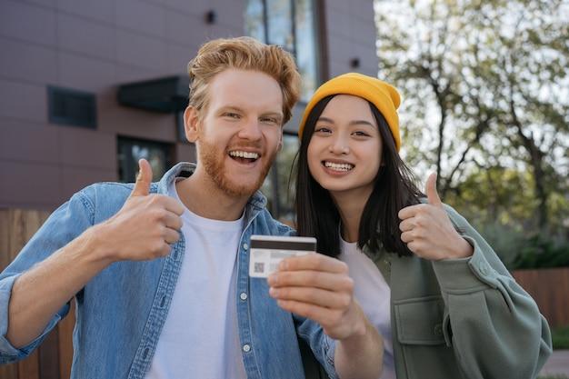 Dois amigos sorridentes segurando um cartão de crédito e mostrando o polegar olhando para a câmera