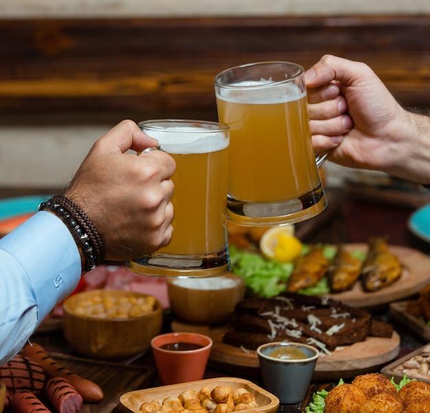 Dois amigos tinindo canecas de cerveja na instalação de cerveja