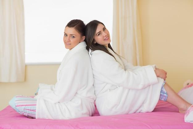 Dois amigos usando roupões de banho sentados de costas