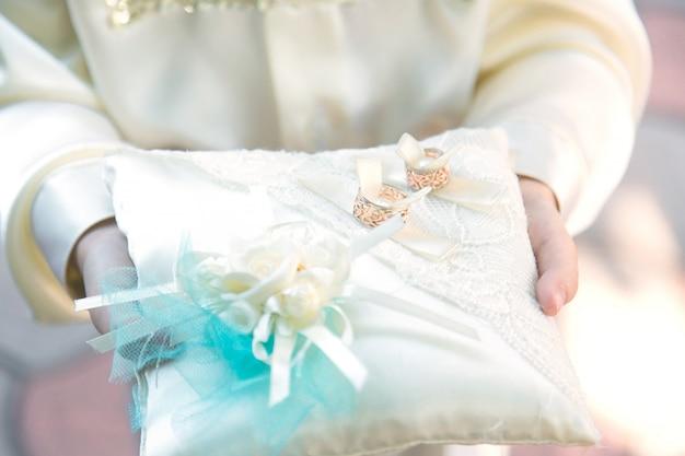 Dois anéis de casamento bonitos em uma almofada nas mãos de uma criança