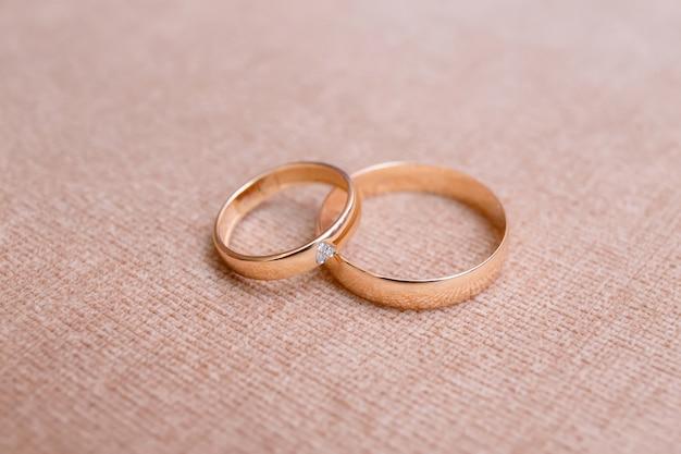 Dois anéis de casamento bonitos na superfície do pano, close-up