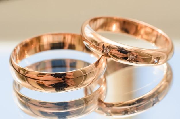 Dois anéis de casamento de ouro com diamantes na superfície