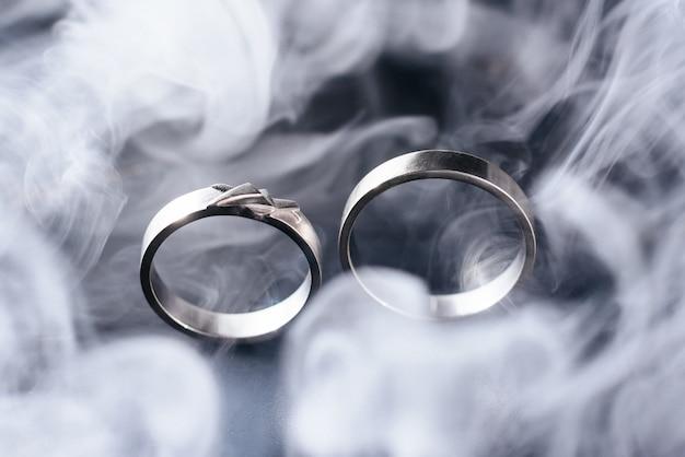 Dois anéis de casamento de ouro com fumaça branca ao redor