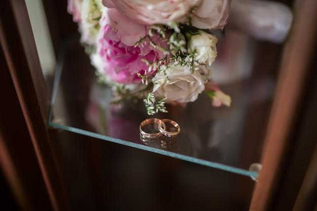 Dois anéis de casamento de ouro e platina e flores primaveris. conceito de casamento.