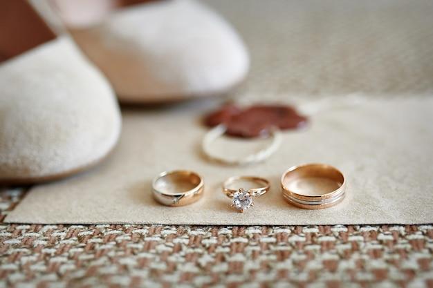 Dois anéis de casamento de ouro e sapatos de noiva