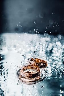 Dois anéis de casamento de ouro em salpicos de água deitado na superfície plana