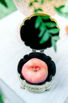 Dois anéis de casamento de ouro em uma elegante caixa de vidro