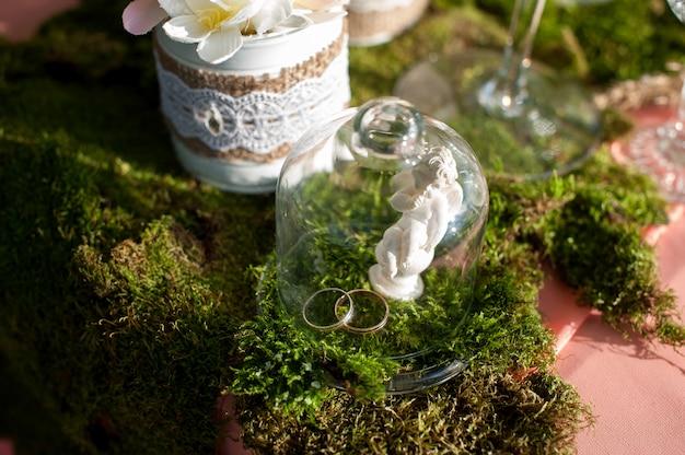 Dois anéis de casamento de ouro em uma mesa sob um copo de vidro